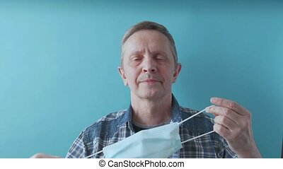 Handsome senior man takes off the medical mask on face and throws away the mask. An elderly man takes off surgical mask. 4k footage