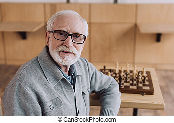 senior man with chess board