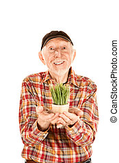 Handsome senior man with grass in small pot