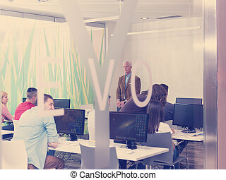 senior teacher and students group in computer lab classroom