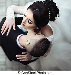 Handsome, sensual groom kissing beautiful bride on the neck closeup, view from above