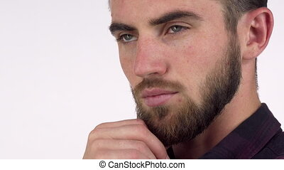 Handsome serious man looking away thoughtfully, rubbing his...