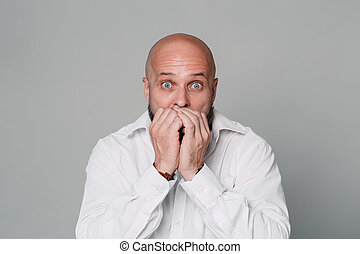 Handsome serious middle-aged man in a white shirt looks at the camera in surprise and holds his hands near his face on a gray background