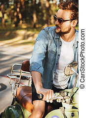 Handsome serious young bearded man sitting on scooter