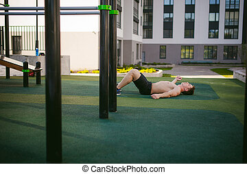 Handsome sexy male bodybuilder athlete man with naked torso Lies on the ground in courtyard. Healthy lifestyle concept.