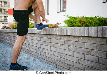 Handsome sexy male bodybuilder athlete man with naked torso, running in morning, outdoors. ties up shoelaces on sneakers. Healthy lifestyle concept.