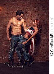 Handsome sexy man holding a girl with a chain. Beautiful girl covers her body with American flag