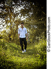 Handsome sexy man outdoors in the garden standing on fresh green grass