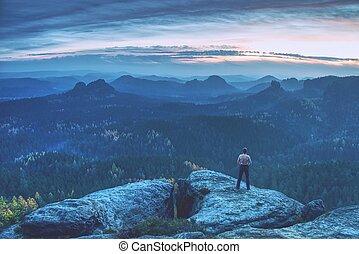 Handsome shirtless man on rocks, runner looking to horizon.
