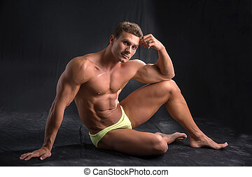 Handsome shirtless muscular man laying down on the floor in bathing suit