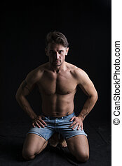 Handsome shirtless muscular man on his knees on dark