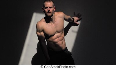 Handsome shirtless muscular man posing against wall -...