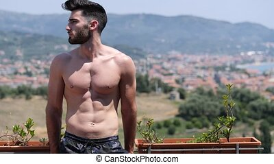 Handsome shirtless muscular young man outdoor on a balcony...