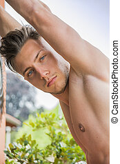 Handsome shirtless muscular young man outdoor, looking at...
