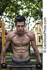 Handsome shirtless young man exercising in outdoor gym in park