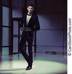 Handsome slim guy wearing black suit