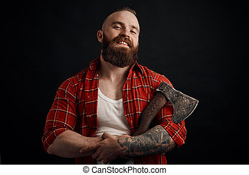 smiling bearded man holding axe looking at camera on black background