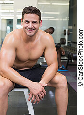 Handsome smiling bodybuilder sitting on bench in weights room