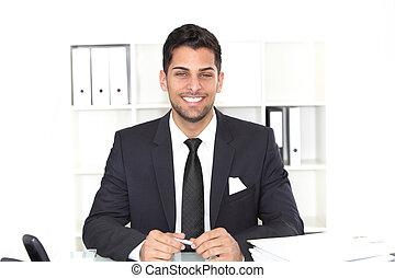 Handsome smiling businessman at his desk