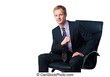 handsome smiling businessman sitting in black office chair