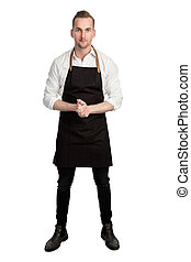 Handsome smiling chef in white and black, holding 2 knifes and a whisk looking at camera standing against a white background.