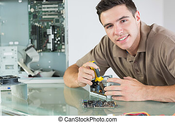 Handsome smiling computer engineer repairing hardware with...