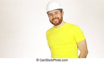 Handsome smiling construction engineer or architect wearing yellow tshirt and white hard hat against light background. 4K shot