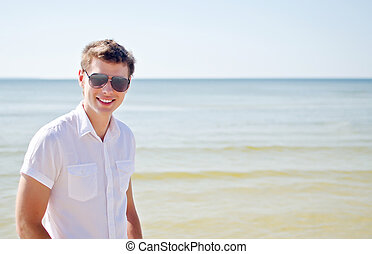 Handsome smiling guy on the beach, with the sea in the background