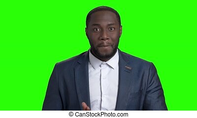 Handsome smiling macho-man on green screen. Sexy african...