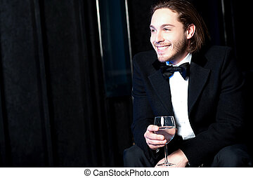 Handsome smiling man holding a glass of wine