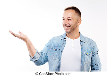 Handsome smiling man pointing at something with hand