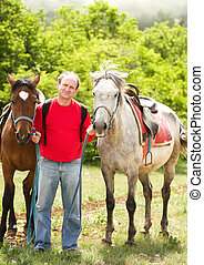 Handsome smiling man with horses
