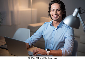 Handsome smiling man working on laptop.