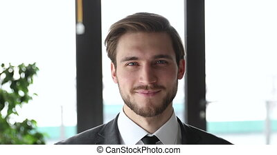 Handsome smiling young professional businessman wearing suit...
