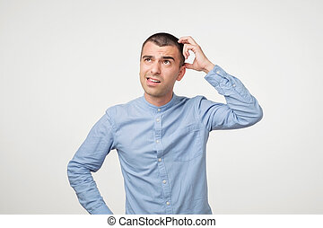 Handsome spanish guy in blue shirt, frowning and looking unsatisfied while scratching head