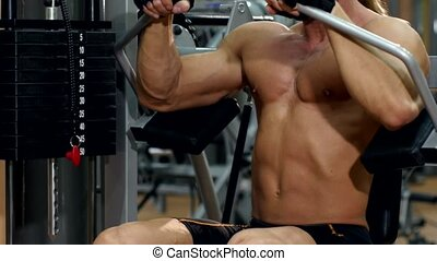Handsome sportsman doing exercises on hands in the gym -...