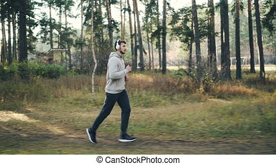 Handsome sportsman is jogging in park and enjoying music in...