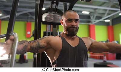 Handsome sporty man is exercising looking into camera in...