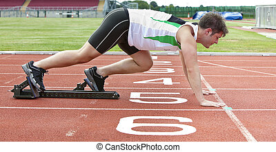 Handsome sprinter on the starting line putting his foot in the starting block in a stadium