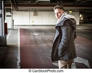 Handsome standing in indoor parking lot in winter