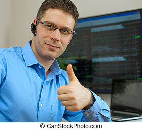 Handsome stock trader with thumbs up in front of computer.