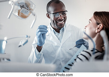 Handsome stomatologist talking to his pretty patient