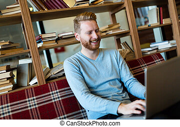 Handsome student working on laptop in bar