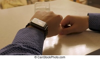 Handsome stylish male managing time on electronic watch....