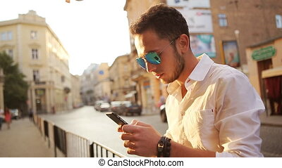 Handsome stylish man chatting on his smartphone outdoors. -...
