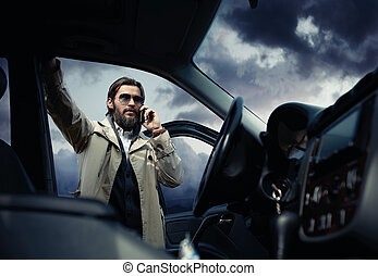 Handsome stylish man on the road next to his car talking on the