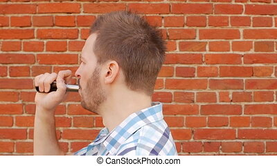 Handsome stylish man smokes vape against a brick wall and...
