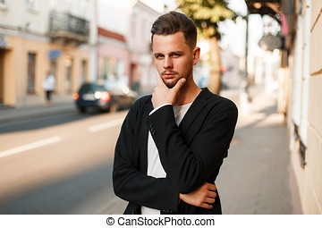 fac71019de8b Handsome stylish young man in business clothes posing on the street