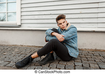 handsome stylish young man with a haircut in a fashionable vintage jeans jacket with black sneakers sits near a wooden wall