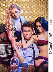 Handsome successful business man having fun in strip club. Beautiful dancers hugging man from both sides